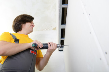 Man using drill to attach drywall panel to wall. Work with plast
