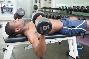 Side view of shirtless man exercising with dumbbells in gym
