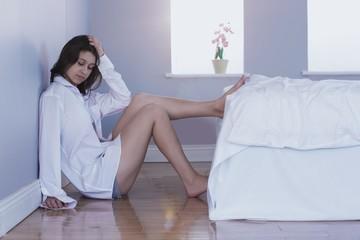 Upset brunette sitting on floor beside bed