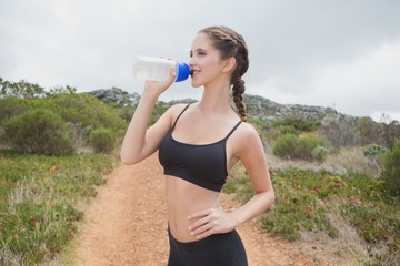 Athletic woman drinking water on country road