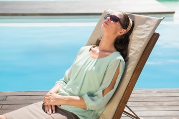 Beautiful woman relaxing on sun lounger by swimming pool