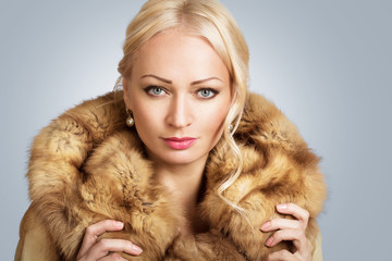portrait of a beautiful blonde young woman wearing fur coat
