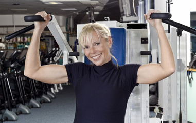 Reife Frau im Fitness Studio an Trainingsgerät Bankdrückmaschi