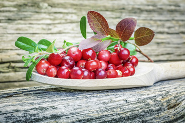 Fresh cranberries with leaves on wooden plank