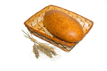 bread in a basket with ears of wheat on a white background