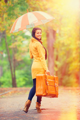 Brunette girl holding suitcase and umbrella at autumn alley in t