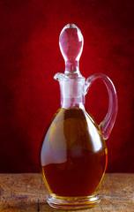 Glaskaraffe mit Olivenöl auf Holztisch und roter Wand