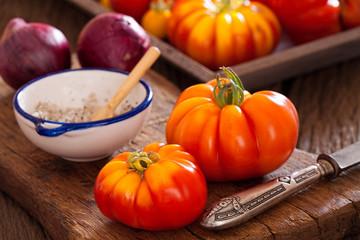 Frische Fleischtomaten mit Messer, Zwiebeln und Salz