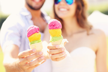 Happy couple showing ice-cream cones