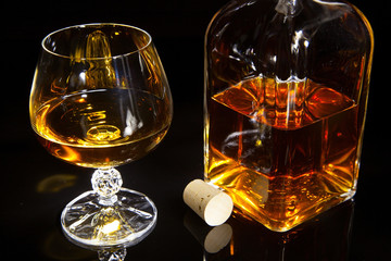 A glass and a bottle of brandy