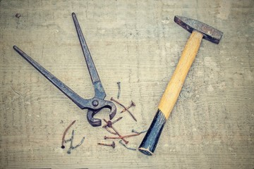 Vintage rusty pliers, hammer and nails, filtered