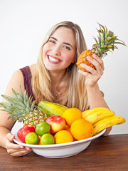 Young healthy beautiful woman with a bowl of fresh exotic fruit