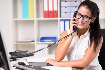 Junge dunkelhaarige Frau telefoniert im Büro