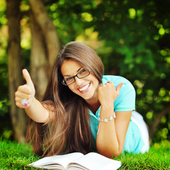 Happy smiling girl in glasses lying in the park near a book and