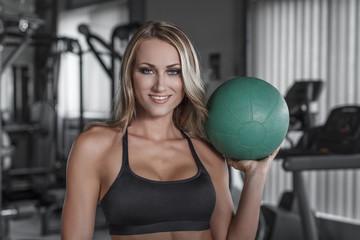 Blonde woman holding medicine ball