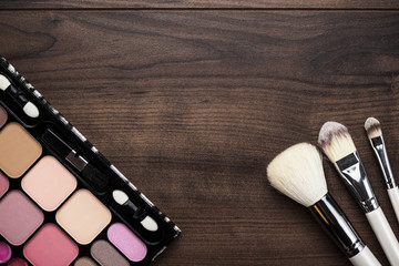 white make-up brushes on wooden background