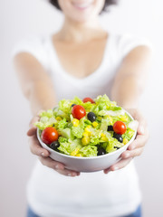 Young woman & vegetable salad isolated in white