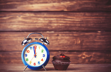 Alarm clock and cupcake.
