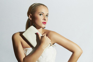 Beautiful blond woman with white clutch.White bride dress