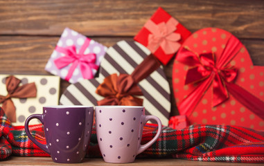 Two cup of coffee and holidays gifts on background.