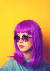 Beautiful girl with violet hair in sunglasses on yellow backgrou
