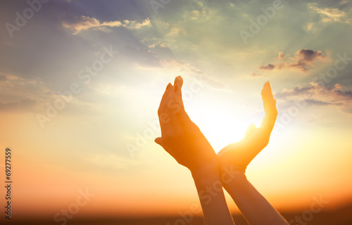 hands holding the sun at dawn - 69277559