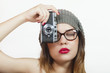 Brunette woman in hipster outfit taking photo with retro camera
