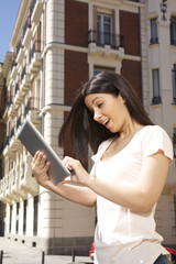 young woman smiling with a digital tablet at street