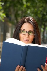 smiling woman with glasses reading a blue book