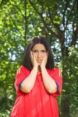 young woman with red spanish football team shirt unhappy.