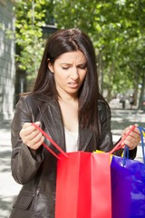 unhappy woman with shopping bags at street in Madrid city Spain.