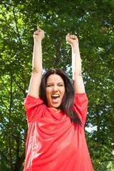 woman with spanish football team shirt cheering happy.