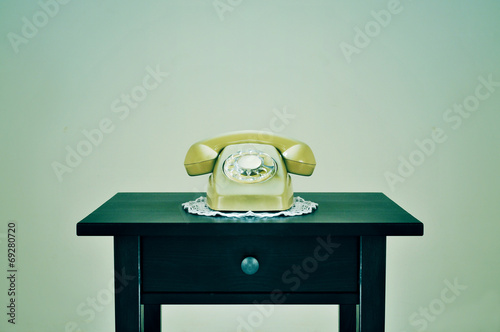old rotary dial telephone on a table, with a retro effect - 69280720