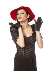 woman with red hat and leather gloves with a kiss gesture