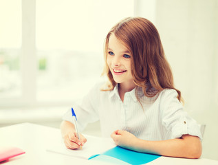 student girl writing in notebook at school