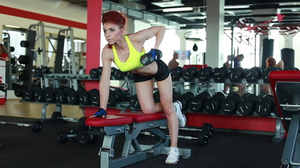 Sexy female athlete exercising with dumbbells