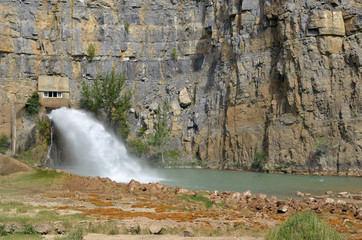 Salida inferior de una presa hidraúlica liberando agua