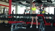 Slender girl training with dumbbells in gym