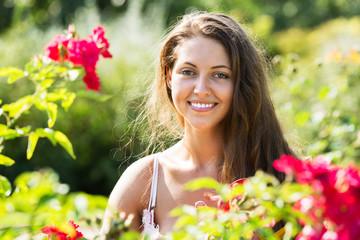 Girl in roses plants at garden