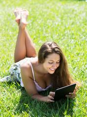 Girl lying on grass with ereader