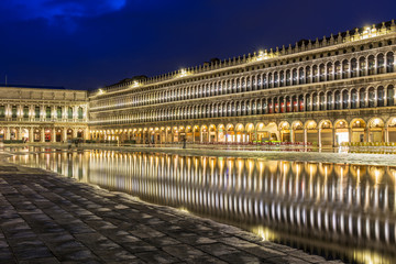 San Marco square with reflection on water at night, Venice.