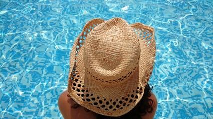 Mujer con sombrero observando piscina