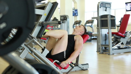 Attractive man doing leg press lying