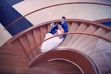 Happy bride and groom on their wedding stand on a wooden ladder