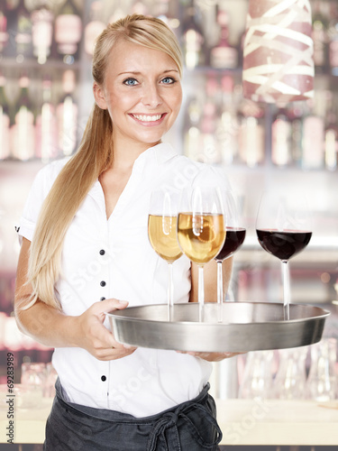 Pretty lady waitress with four glasses of wine - 69283989