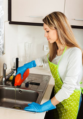 woman cleaning pipe with detergent