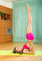 Cheerful girl doing yoga at home