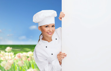 smiling female chef with white blank board