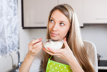 Smiling woman eating curd cheese