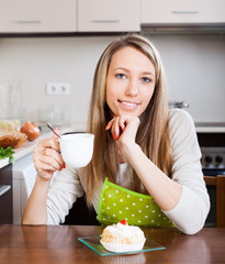 Smiling woman in apron drinking tea with cake